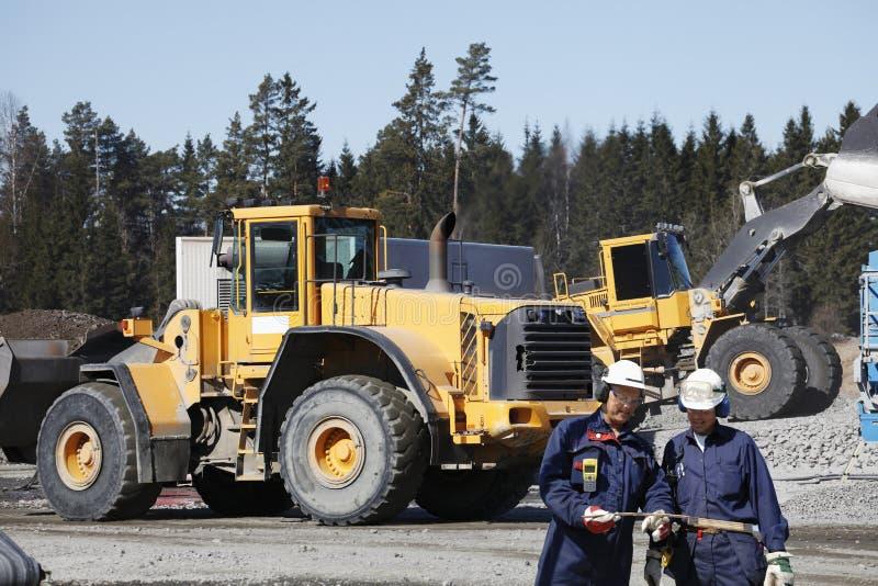 Bouteurs, camions et travailleurs images stock