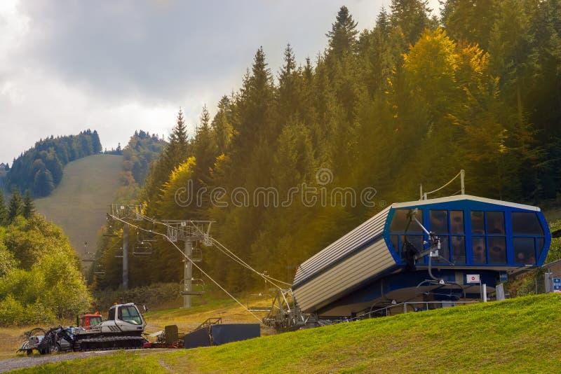 Bouteurs inférieurs de base et de chasse-neige de télésiège dans une scène chaude de montagne de rayon de soleil photos libres de droits