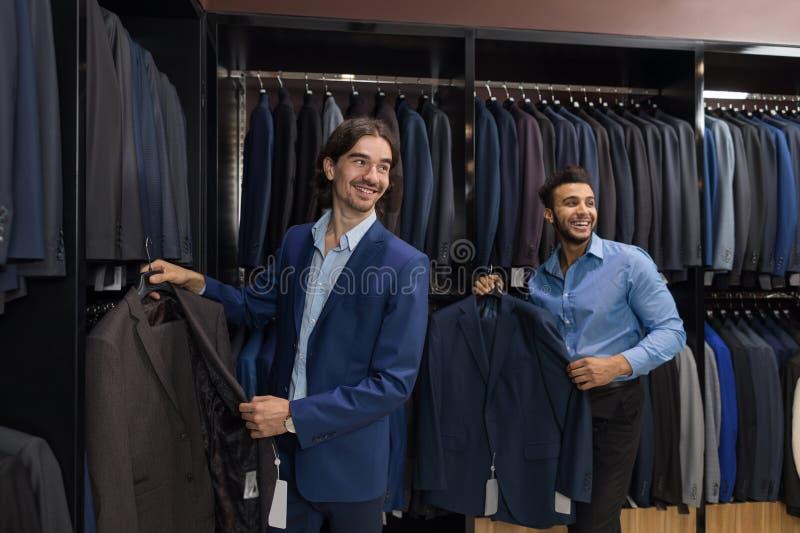 Boutique belle de mode d'homme d'affaires, clients choisissant des vêtements dans le magasin de détail images stock