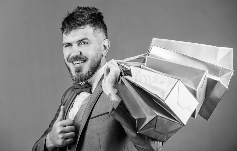 Boutique dell'elite L'uomo d'affari elegante barbuto dell'uomo porta i sacchetti della spesa su fondo grigio Renda comperando pi? fotografia stock libera da diritti