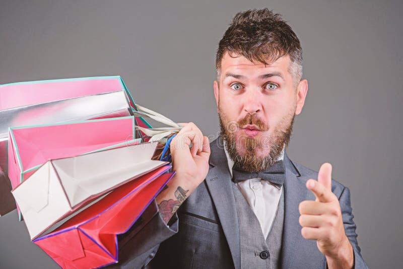 Boutique dell'elite Renda comperando pi? allegro L'uomo d'affari elegante barbuto dell'uomo porta i sacchetti della spesa su fond immagini stock libere da diritti