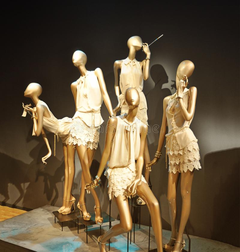 Boutique display window with mannequins. Boutique display window with gold mannequins royalty free stock image