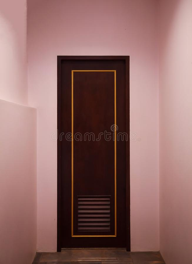 Boutique vintage retro wooden door made from plain tropical dark brown textured wood panel board with pink color painted wall back stock photos