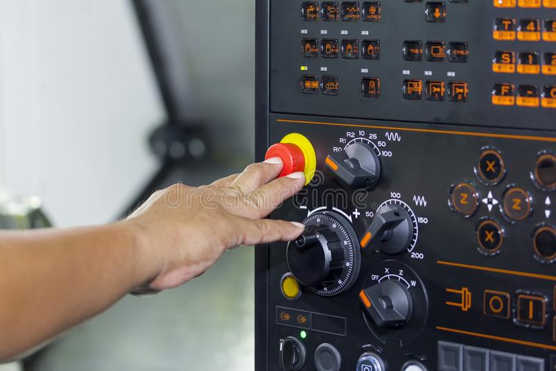Bouton d'arrêt d'urgence de presse de doigt d'utilisation d'opérateur de machine de tour de commande numérique par ordinateur de  photographie stock libre de droits