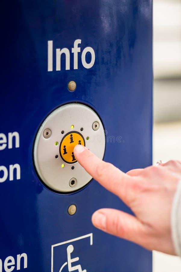 Bouton d'infos de pressing de femme de machine d'aide dans la station de train images libres de droits