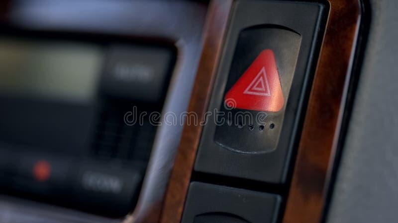 Bouton de avertissement de clignoteur de risque de voiture sur le tableau de bord, menace de situations d'urgence image libre de droits