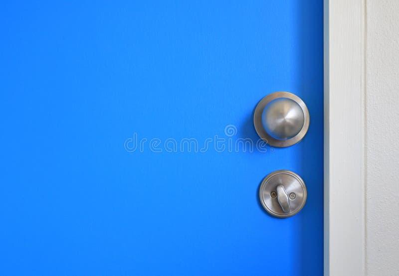 Bouton inoxydable en gros plan et verrou sur la porte bleue avec l'espace de copie images stock