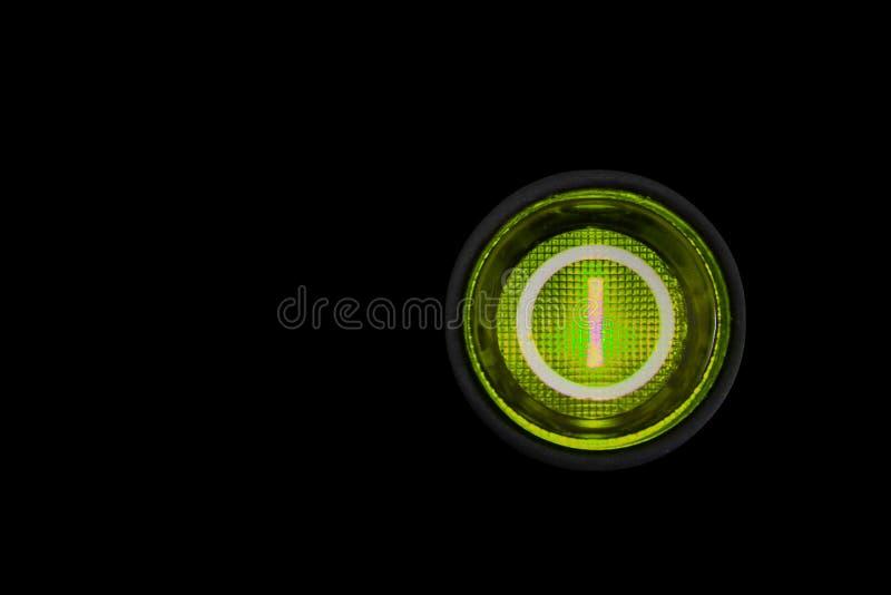 Bouton marche-arrêt ou commutateur d'énergie verte ronde avec la rétro illumination rougeoyant dans le macro foncé photo stock