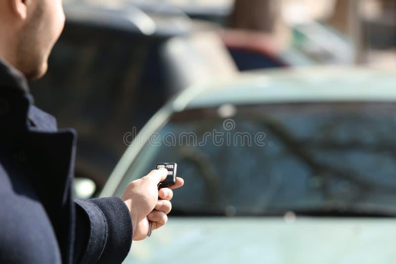 Bouton-poussoir d'homme sur à télécommande du système d'alarme de voiture, dehors photos libres de droits