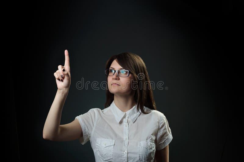 Bouton poussoir de femme avec le doigt au-dessus du fond noir image stock