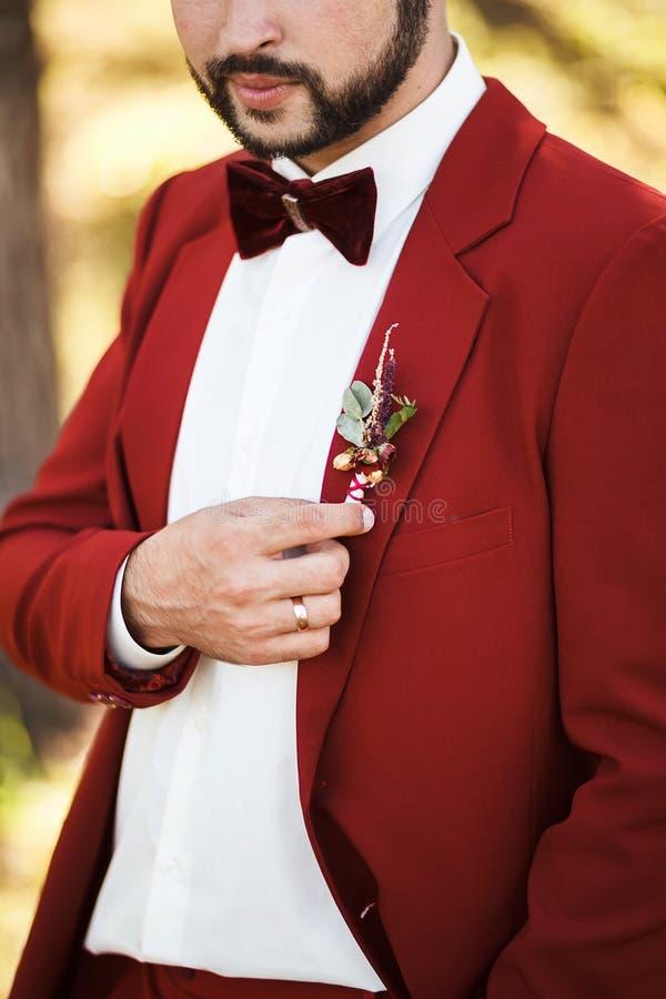 Boutonniere übersetzt zum Knopfloch Bräutigam in der roten Klage mit stilvollen Bart und dem Schnurrbart lizenzfreie stockfotografie