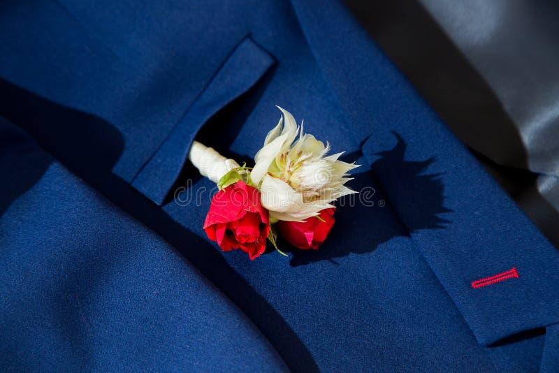 Boutonniere accessorio dello sposo il piccolo rivettato alla tasca del suo rivestimento fotografie stock libere da diritti