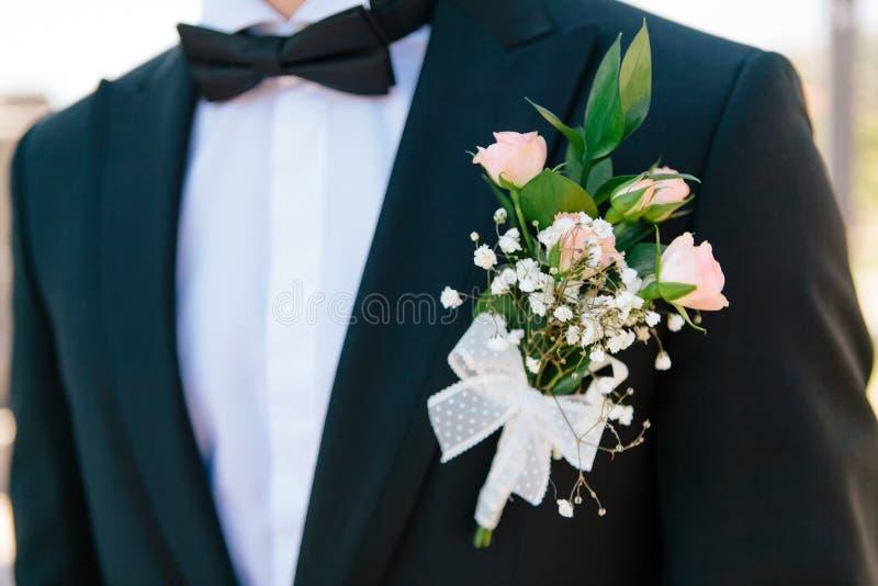 Boutonniere con la decorazione su un rivestimento elegante blu scuro degli sposi, fuoco selettivo delle rose di rosa del primo pi fotografia stock