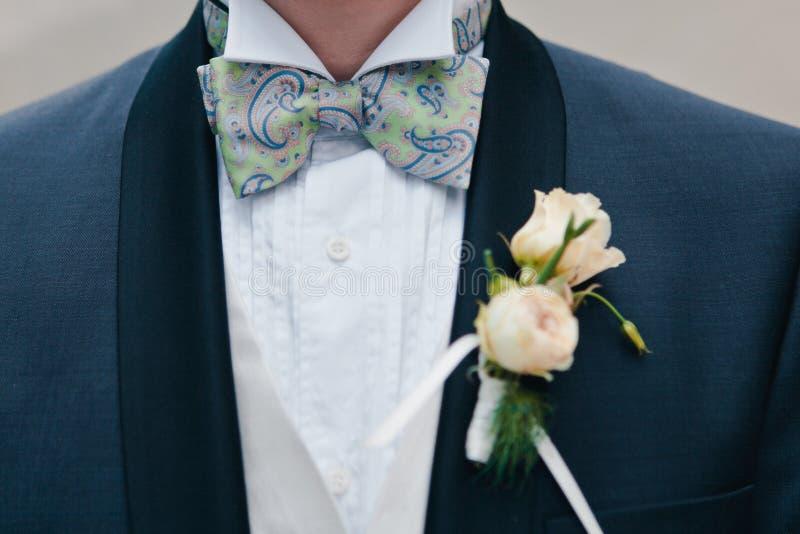 Boutonniere con la decorazione su un rivestimento elegante blu scuro degli sposi, fuoco selettivo delle rose di rosa del primo pi immagine stock libera da diritti
