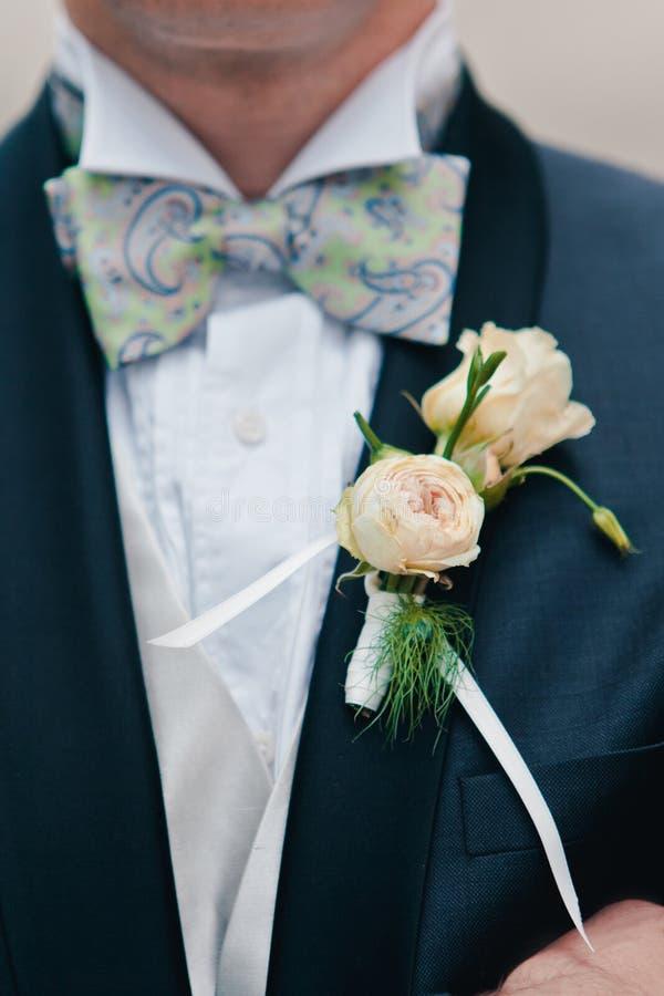 Boutonniere con la decorazione su un rivestimento elegante blu scuro degli sposi, fuoco selettivo delle rose di rosa del primo pi fotografie stock libere da diritti