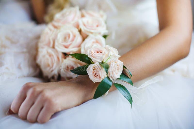 Boutonniere del braccialetto sulla mano della sposa, mazzo nuziale fotografie stock libere da diritti