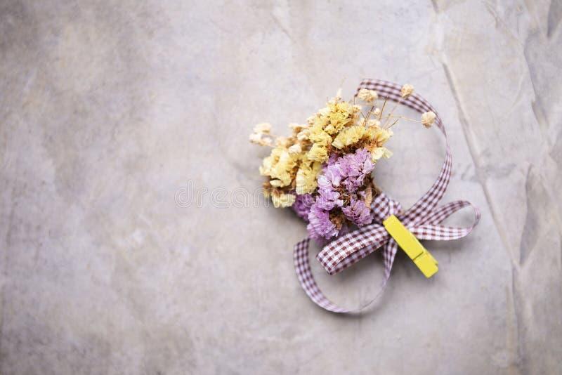 Boutonniere des fleurs pourpres et jaunes mélangées sèches avec le ruban pourpre photographie stock