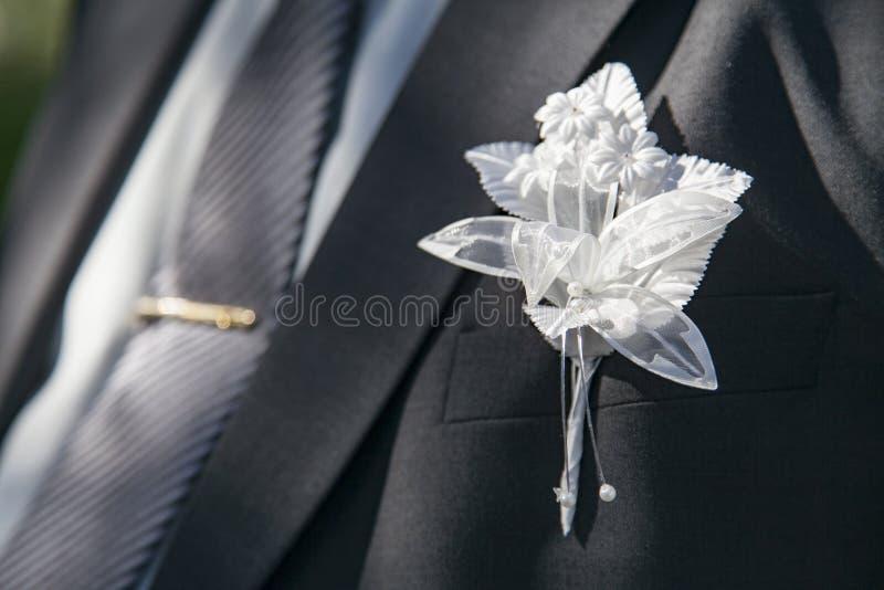 Boutonniere di nozze sul vestito dello sposo immagine stock
