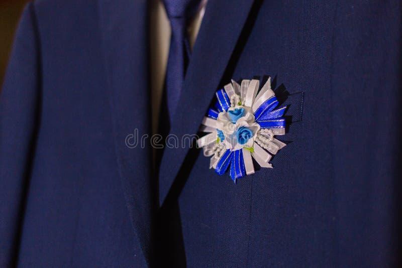 Boutonniere elegante de la flor del novio, situado en la chaqueta a cuadros azul elegante del novio imagen de archivo