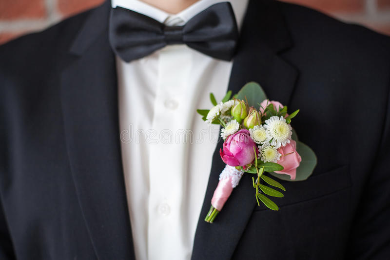 Boutonniere pinned on man in black suit stock image