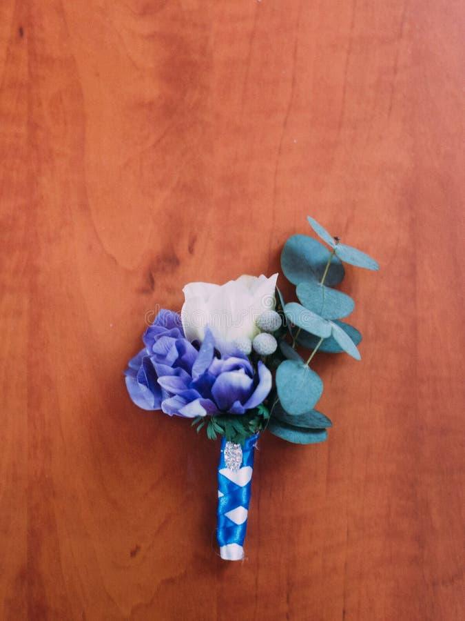 Boutonniere sveglio di nozze con i fiori bianchi e viola nel fondo di legno fotografia stock libera da diritti
