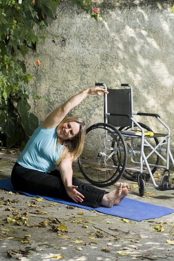 Bouts droits de femme à côté de fauteuil roulant - verticale image libre de droits