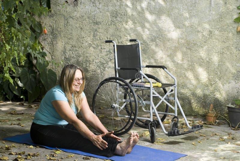Bouts droits de femme à côté de fauteuil roulant - verticale image stock