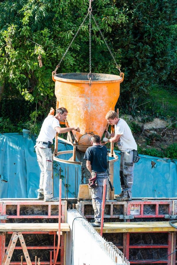 Bouw bouwarbeiders bij bouwwerf gietend beton in vorm stock foto