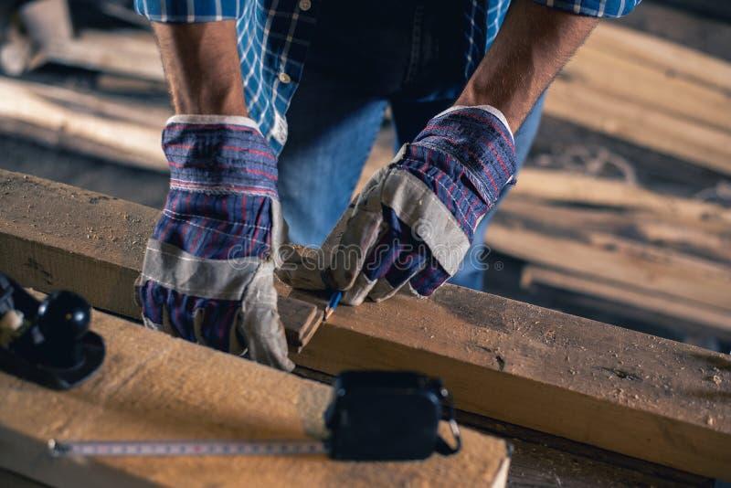 Bouw, dakwerk, houtbewerking Het close-up van de handen van een timmerman, een arbeider met een potlood maakt een teken op een ho royalty-vrije stock afbeeldingen