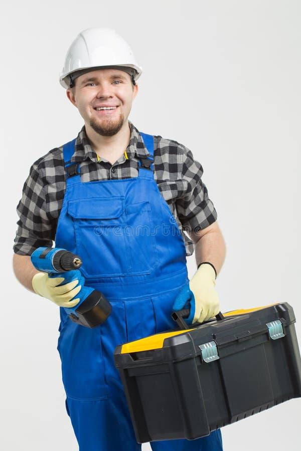 Bouw, de bouw en arbeidersconcept - Knappe toolbox en de schroevedraaier van de bouwersholding op witte achtergrond royalty-vrije stock afbeeldingen