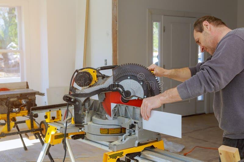 Bouw die huis remodelleert dat het houten versieringsbasis vormen met cirkelzaag snijdt royalty-vrije stock afbeelding