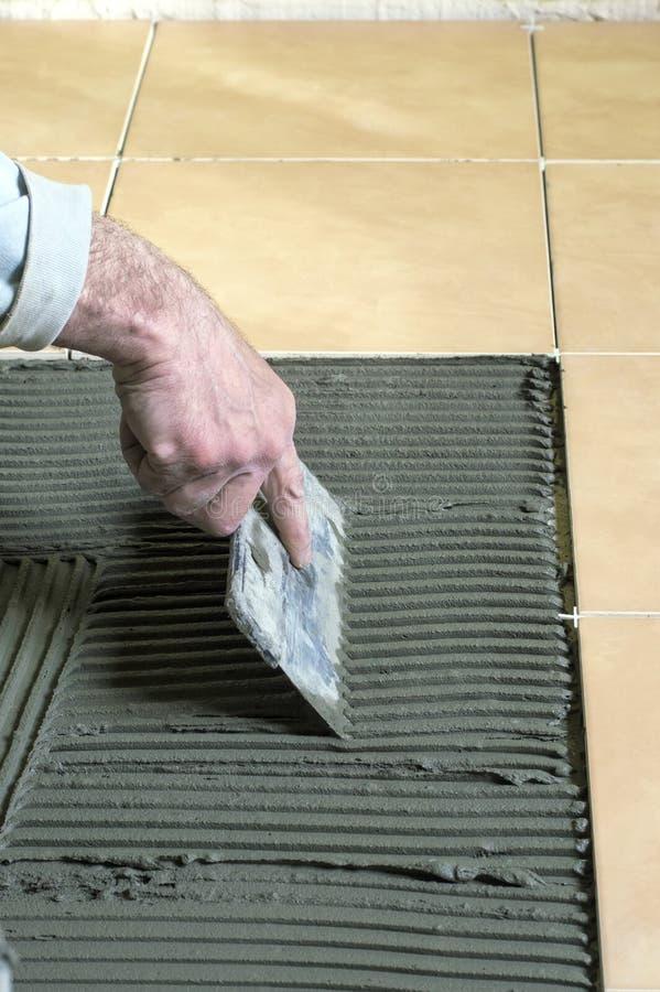Bouw, die tegels, de troffel van het het werkgebruik leggen stock afbeelding