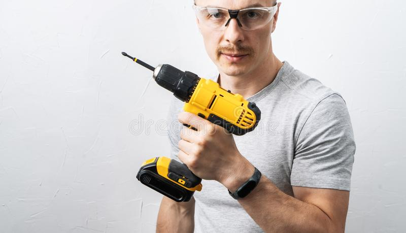 Bouw: Een mens in beschermende glazen houdt een gele elektrische schroevedraaier stock foto's