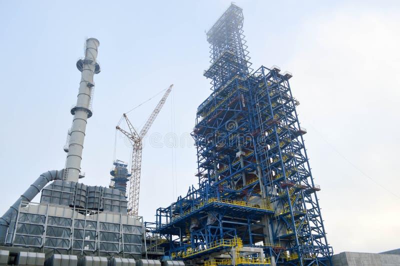 Bouw met kranen van een grote blauwe chemische installatie bij een olieraffinaderij stock foto's