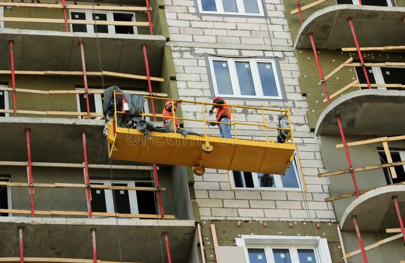 Bouw opgeschorte wieg met arbeiders op een onlangs gebouwd high-rise gebouw stock foto's