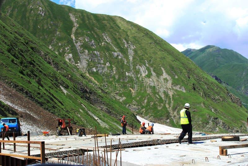 Bouw van de brug in de bergen Concrete plakken met metalware en verscheidene arbeiders en hun voorman stock afbeelding