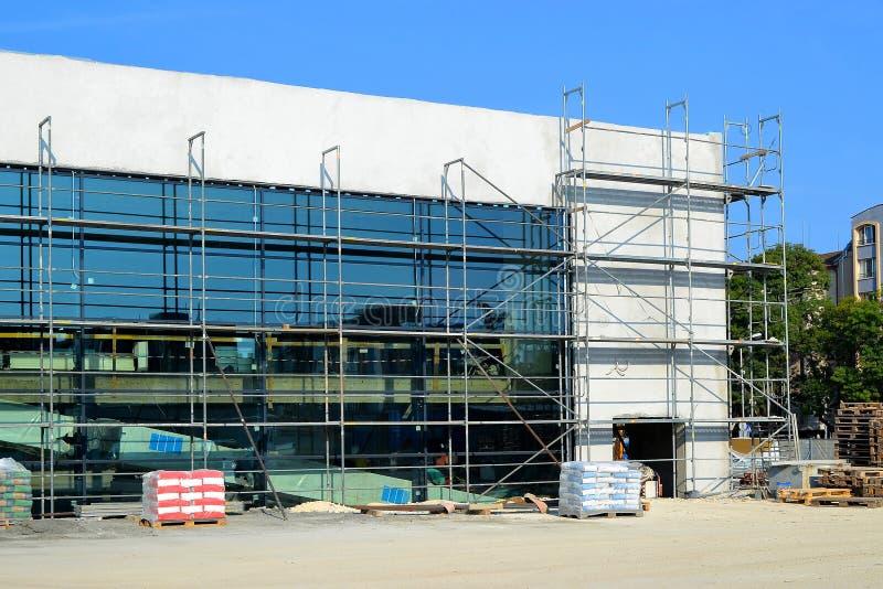 Bouw van een modern winkelcentrum met een voorgevel van glas en beton en een ondergronds parkeren, in een zonnige dag met een blu royalty-vrije stock foto