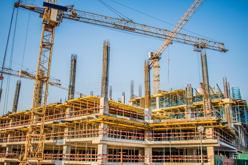 bouw van een winkelcentrum met grote materiaalkranen stock afbeelding