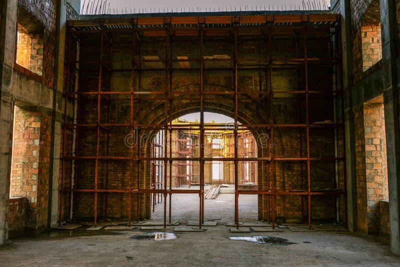 Bouw van het gebouw Grote boog van baksteen In aanbouw bouwend steiger op een huis Concrete vloer stock fotografie