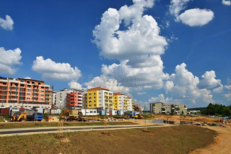 Bouw van nieuwe huizen Concept voor de industrie Kraan en blauwe hemel met wolken en zon Bouwconstructieplaats bij zonsondergang royalty-vrije stock foto's