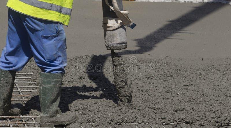 Bouwbouwvakker gietend cement of beton met pompbuis stock foto's