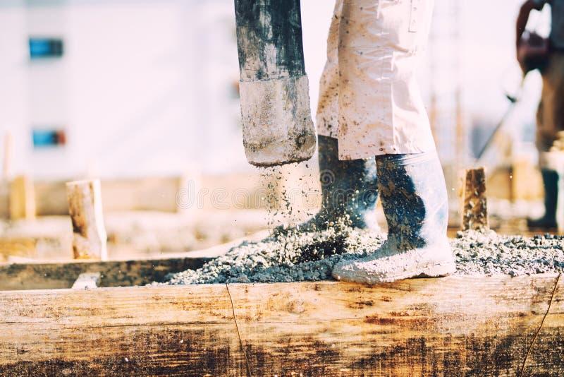 Bouwdetails - arbeider die cement of beton met automatische pomp leggen stock fotografie