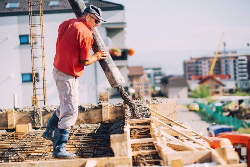 Bouwdetails - arbeider het leggen cementeert of beton met automatische pomp bij huisbouw stock foto
