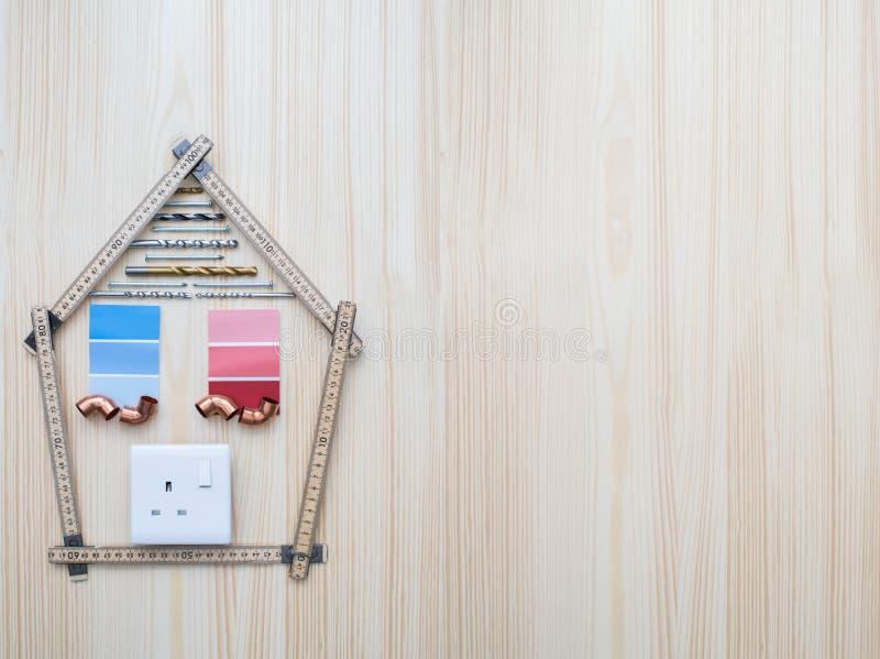 Bouwend Componenten in Vorm van Huis worden geschikt op Houten Backgro die stock afbeeldingen