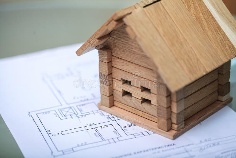 Bouwend huis op blauwdrukken met arbeider - bouwproject stock fotografie