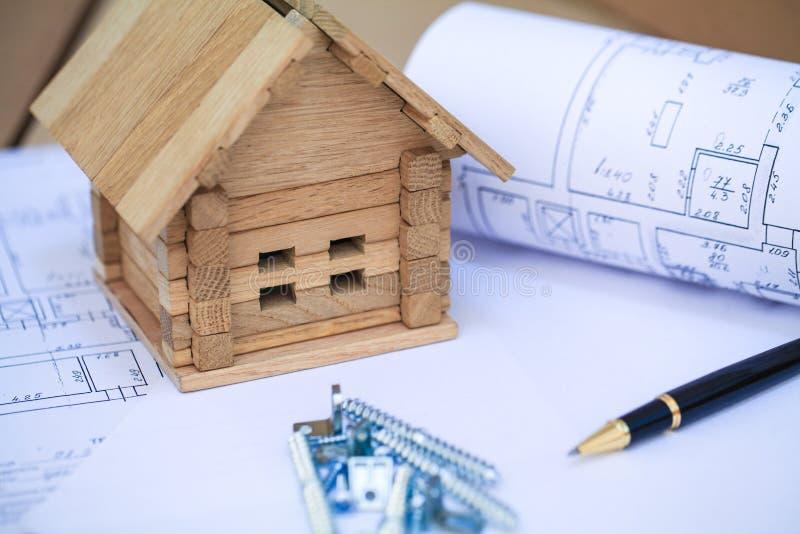 Bouwend huis op blauwdrukken met plan - bouwproject stock afbeelding
