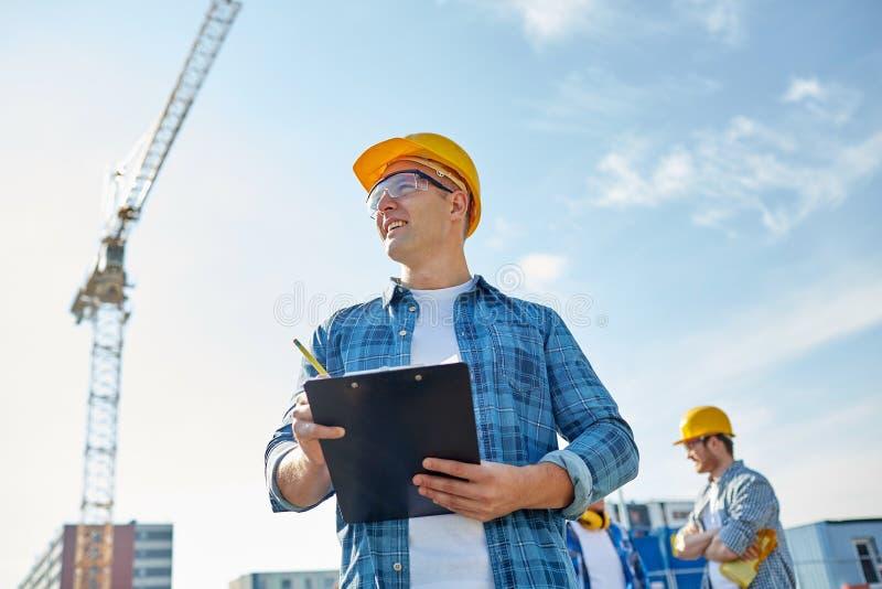 Bouwer in bouwvakker met klembord bij bouw royalty-vrije stock afbeeldingen