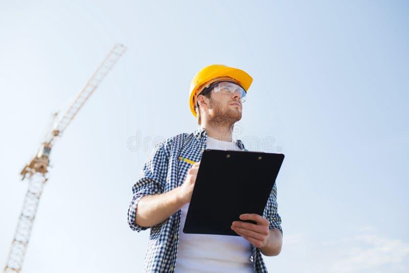 Bouwer in bouwvakker met klembord in openlucht royalty-vrije stock fotografie