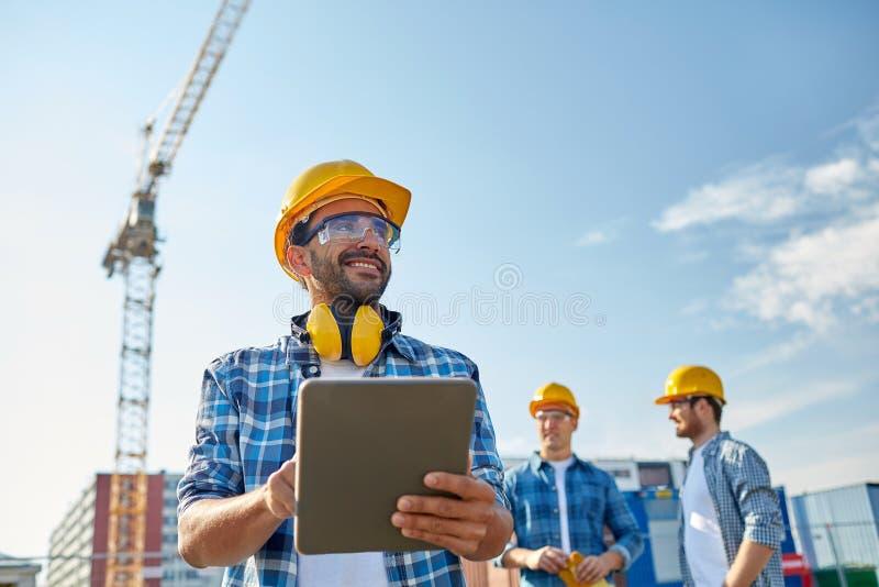 Bouwer in bouwvakker met tabletpc bij bouw stock fotografie