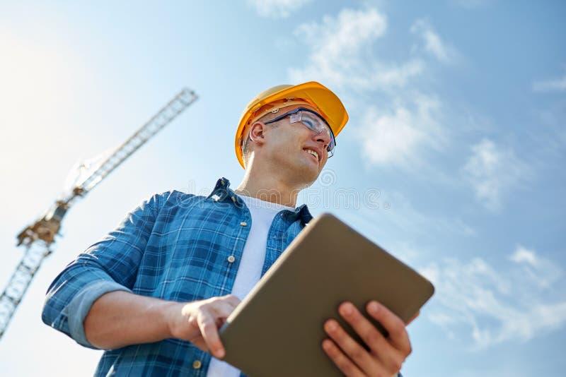 Bouwer in bouwvakker met tabletpc bij bouw royalty-vrije stock fotografie